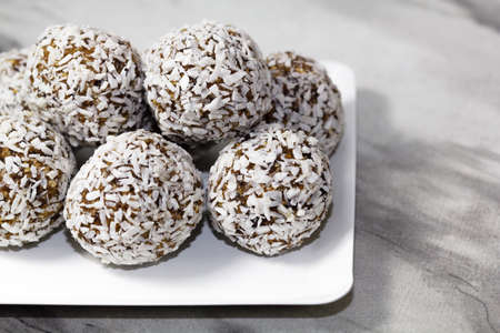 Homemade energy balls with dried apricots, raisins, dates, prunes, walnuts and coconut. Healthy sweet food. Energy balls in a plate on a marble gray background. Close up. Side view. Copy space