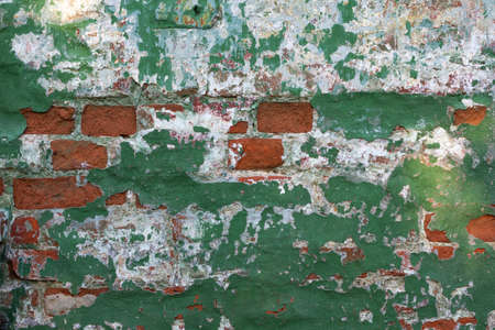Green and white brick background. Dilapidated brick wall. Grunge texture is a green brick wall. Green old plaster on the wall. Copy space.