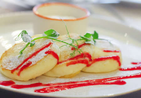 Cheesecakes with sour cream. Yummy dessert. Cheesecakes on a white plate. Traditional Russian dish. Close-up.