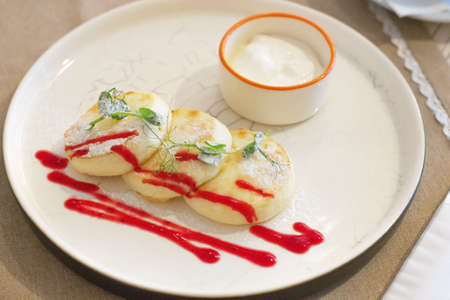 Cheesecakes with sour cream. Yummy dessert. Cheesecakes on a white plate. Traditional Russian dish. Close-up. View from above.