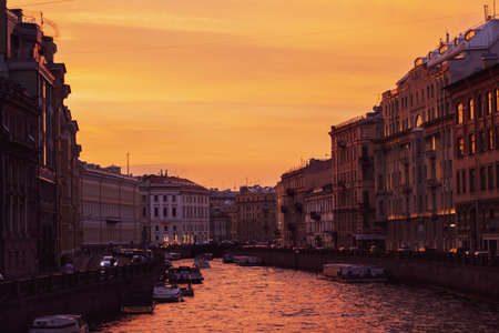 Orange sunset in St. Petersburg on the Moika River. The architecture of St. Petersburg in the sunset light on the river bank.