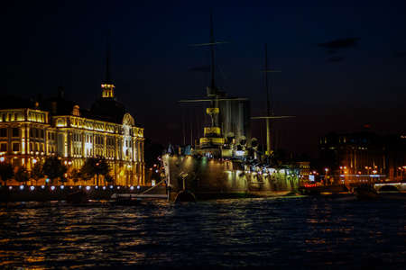 Saint Petersburg, Russia, July 2021: Ship Aurora in St. Petersburg at night. Night landscape of the Neva River and Aurora.