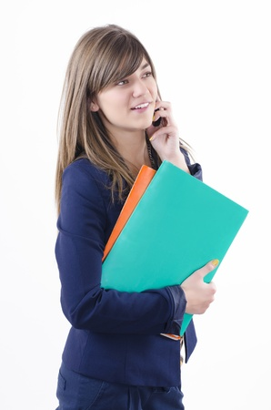 bussines people: beautiful young business woman holding orange and green folder in her hand and talking on the phone