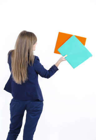 Girl in business clothes in a jacket and trousers turned back holding folders with hand raised up photo