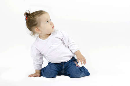 curiously: cute little girl squatting on his knees and leaning with one hand on the ground looking up curiously