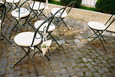 Decorated Outdoor Wedding Ceremony With White Wrought Iron Chairs