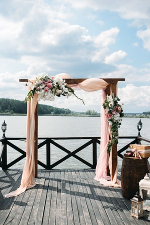 wedding arch decorated with flowers on the river side 스톡 콘텐츠