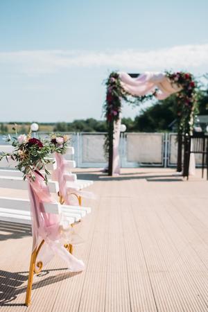 Arco de boda decorado con flores de borgoña y eucalipto, bancos blancos para invitados decorados con flores y cintas Foto de archivo - 96863757