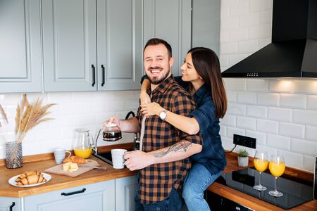 A very happy guy with a beard and a tattoo on his hand pours himself coffee from a coffee pot while standing in the kitchen, a beautiful young brunette girl hugs him from the back 版權商用圖片