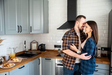 Couple heureux dans la cuisine le matin câlins. Sur la table sont des viennoiseries fraîches, croissants, jus d'orange