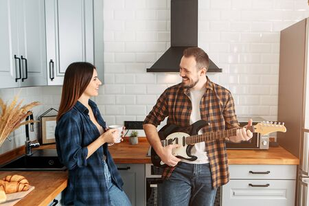 Couple in casual clothes at home in the kitchen. Guy with electric guitar, girl with coffee