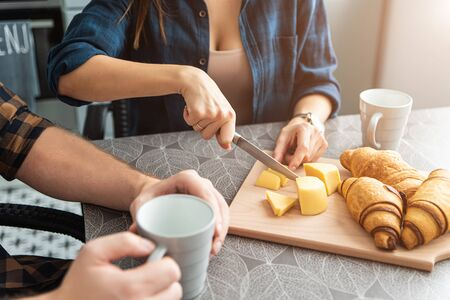 Couple at breakfast. A guy with a cup of coffee, a girl cuts cheese and bread. Their faces are not visible Foto de archivo - 138299737