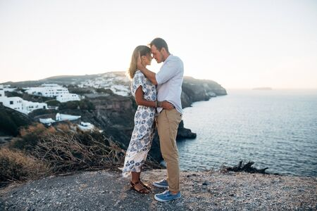 Beautiful couple stand on the edge of a cliff and hug passionately at sunset