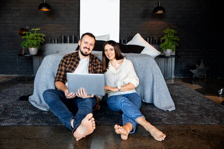 Gadgets in family life. Husband and wife with a laptop spend their leisure time watching videos and on social networks