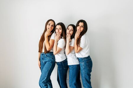 Emotional photo of a group of girls in white t-shirts. They cover their mouths with their hands. Isolated photo