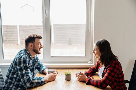 Married couple in the kitchen in a relaxed atmosphere. Young husband and wife talk in the kitchen sitting at the table, they drink coffee Archivio Fotografico
