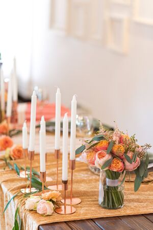 Festive banquet decor in peach color. Bouquet of roses flowers and candles in candlesticks