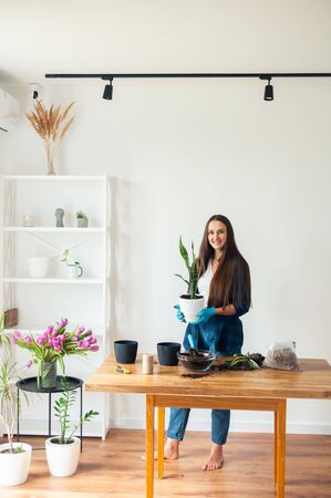 A young woman in a casual checkered shirt is gardening at home. A girl is standing with a pot in her hands and smiling indoors with a white wall in the background.