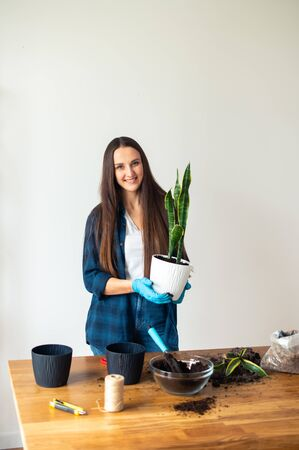 A girl in protective gloves holds a flowerpot. The concept of landscaping at home. Home lifestyle and hobbies. Isolated image on a white background.