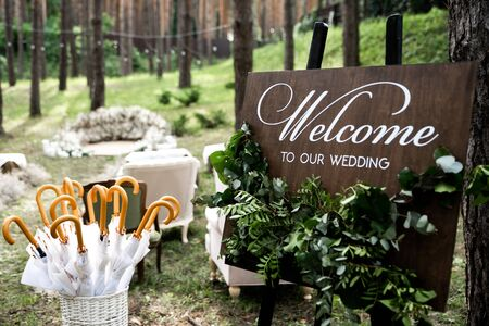 Rustic style wedding decor. Outdoor wooden welcome board decorated with green branches, basket with umbrellas in case of rain