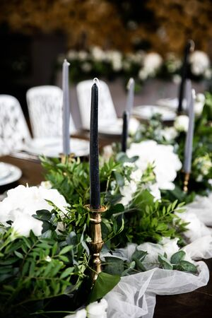 Gray candles in candlesticks among greenery on the festive table