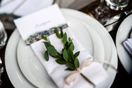 Guest card on the white napkin with branche of eucalyptus and beige ribbon