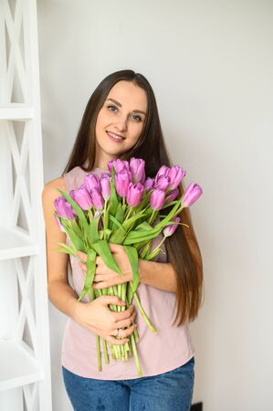 Young attractive girl with fresh flowers tulips. Spring mood, colorfull and pastel colors. Indoor image on a white background