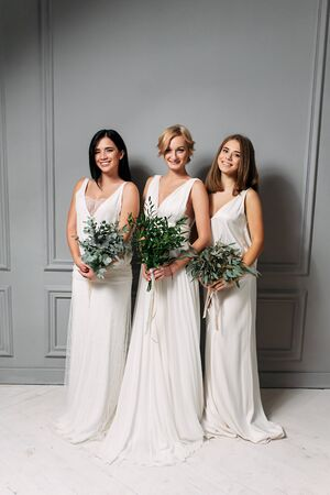 Wedding day. Bridesmaids in elegant white dresses in the studio with a gray background, bouquets of green branches in their hands.