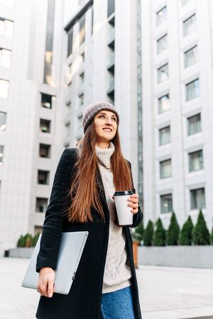 Morning in the business center of the city. A young woman in a coat with coffee and a laptop in her hands among business skyscrapers. She smiles