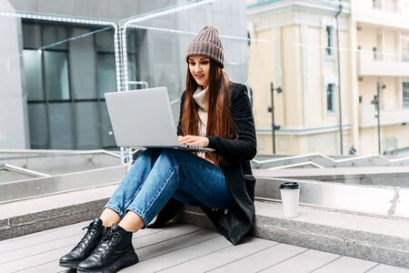 Girl freelancer with a laptop works sitting on a step on the street. She is in casual clothes