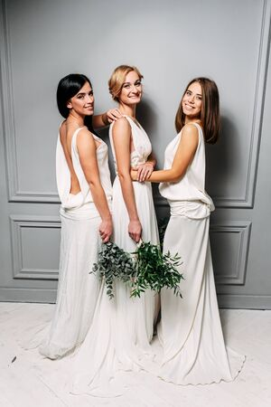 Stylish wedding shooting in the studio. A group of girls in beautiful long dresses with bouquets in their hands Standard-Bild