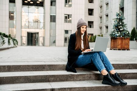 A student uses a laptop to study. She is sitting on the steps outdoors, looking at the camera and smiling. Cold season, a woman wearing a coat and hat