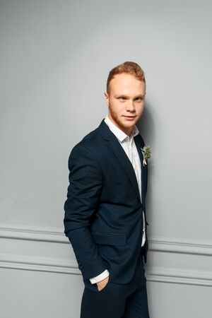 Elegant and attractive red-haired guy in a suit in the studio with a gray wall on the background. Image of a groom or best man with a buttonhole