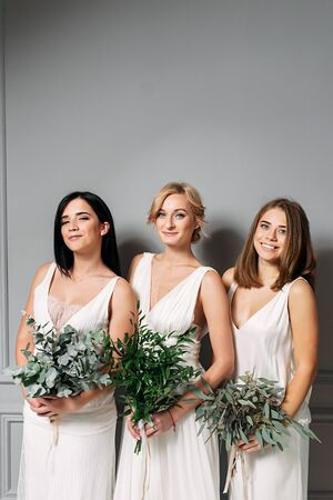 Wedding day. Three different girls in wedding dresses with bouquets in their hands. They are laughing. close-up portrait Standard-Bild