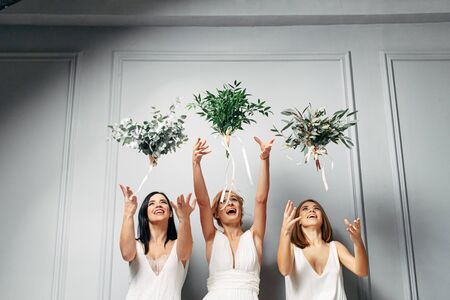 Wedding customs. Bridesmaids in themed similar outfits throw bouquets and laugh. Studio photo
