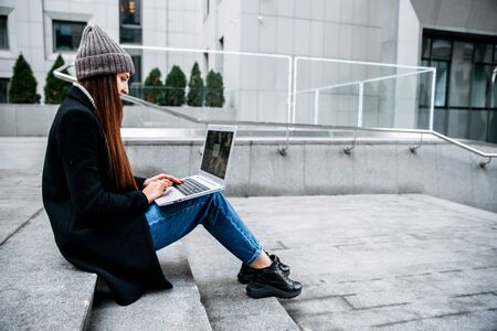 A young woman with a laptop in a casual coat and hat in the business center of the city, she looks at the laptop screen while sitting on the concrete steps. Side view Zdjęcie Seryjne