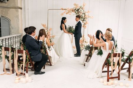 I promise to always love you. A couple of newlyweds make vows in front of the altar, they look into each others eyes. Wedding ceremony indoors. Banco de Imagens