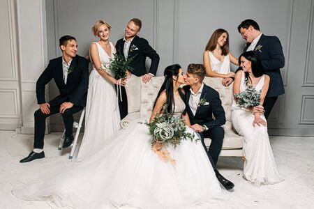 The idea of a group photo at a wedding. Beautiful newlyweds of love are sitting on the couch and kissing, their bridesmaids and best men are posing. Bridesmaids in similar ivory dresses Standard-Bild