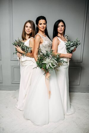 Friendship of women. Bride and bridesmaid three together. They have bouquets of green branches of eucalyptus and other plants in their hands.