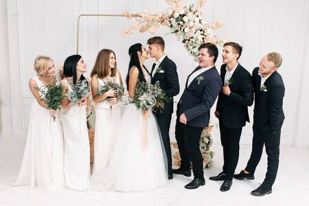 Fun wedding group photo. Bride and groom kiss, bridesmaids and best men glance and laugh