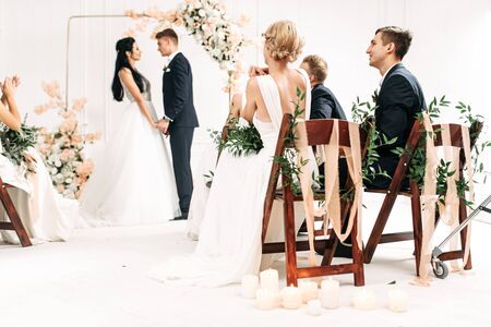 Stylish wedding ceremony decorated with flowers and green branches. A couple of bride and groom near the arch holding hands, guests are sitting on chairs