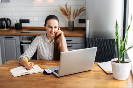Work at home. A young woman uses a laptop to work in the kitchen. She writes something in a notebook with a pen and speaks on the phone