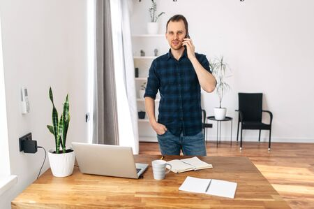 Office at home. A young man in a bright modern office space speaks on a mobile phone. On the table laptop, notebook for notes