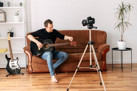 Online guitar lessons for beginners. A young guy with an acoustic guitar records video lessons, guitar tutorial. Online tutor, mentor 版權商用圖片