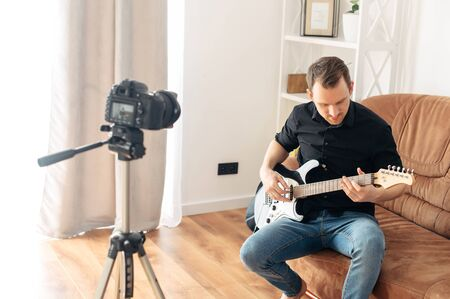 Learning to play musical instruments online, guitar playing tutorial. The guy is recording a training video how to play the bass guitar. Online mentor, tutor