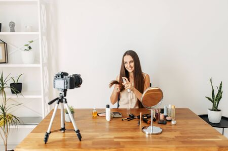 Video recording tutorial of hair care, beauty blogging. The girl applies the product for dry and damaged hair ends, she sits in front of the camera on a tripod