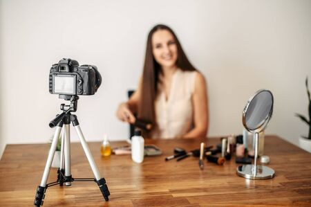 Online learning concept. Beauty industry, beauty blogs. The camera on a tripod shoots a woman with long hair. Woman out of focus, cosmetics and mirror on the table