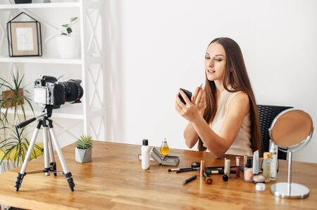 Makeup tutorial, beauty blogs. Young attractive woman is applying lip makeup and recording video with a camera.