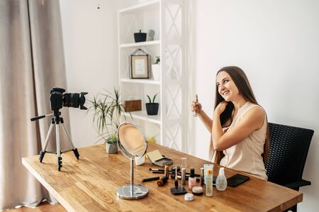 A young woman is recording a video of hair care products. She sits at a table opposite the camera on a tripod and sprays the care product on her hair. Beauty blogging concept