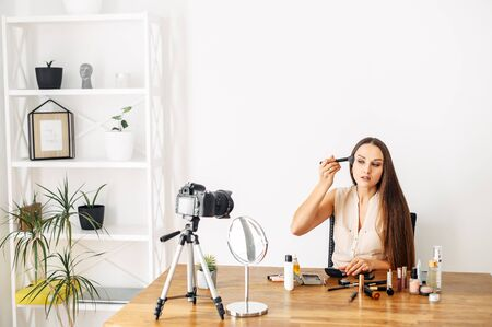 Makeup tutorial, beauty blogs. A young attractive woman is recording video tutorials on how to make a self make-up. She sits with a brush and applies bronzer, blush or powder.